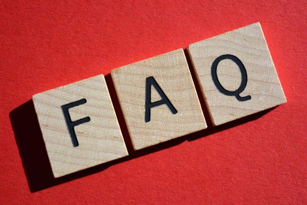 FAQ acronym for Frequently Asked Questions in 3D wooden alphabet letters on a bright red background